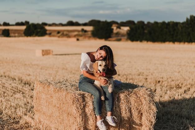 Mulher bonita jovem andando com seu cachorro retriever dourado em um campo amarelo ao pôr do sol