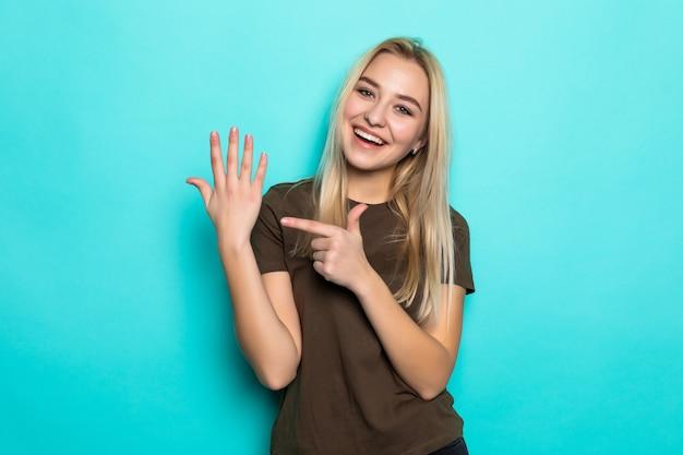 Mulher bonita jovem apontou no dedo isolado na parede azul