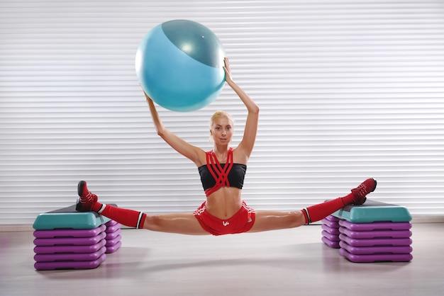 Mulher bonita jovem aptidão flexível fazendo espacate durante seu w