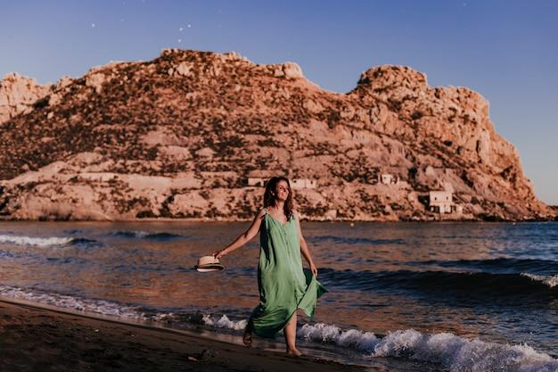 Mulher bonita jovem caminhando na praia ao pôr do sol