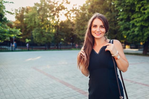 Mulher bonita jovem caminhando no parque de verão. senhora elegante vestindo roupa elegante.