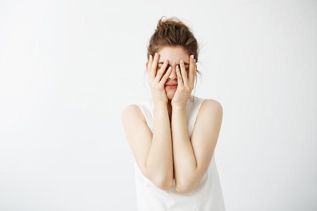 Mulher bonita jovem cansada entediada, escondendo o rosto atrás das mãos.