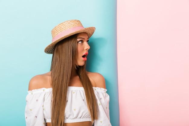 Mulher bonita jovem chocada posando usando chapéu isolado.