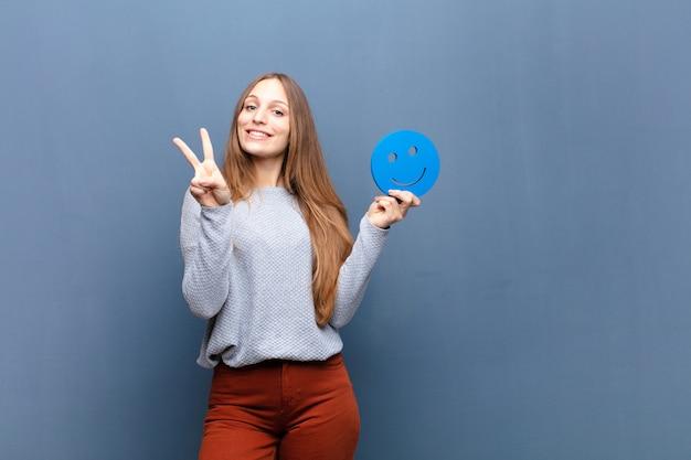Mulher bonita jovem com uma parede azul de rosto sorridente com um espaço de cópia