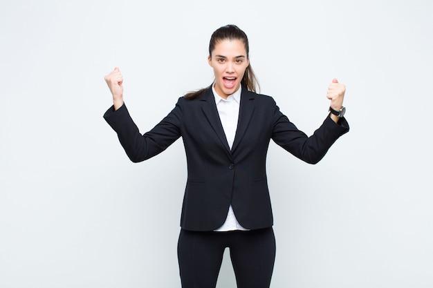 Mulher bonita jovem comemorando um sucesso inacreditável como um vencedor, parecendo animado e feliz dizendo, pegue isso! conceito de negócios