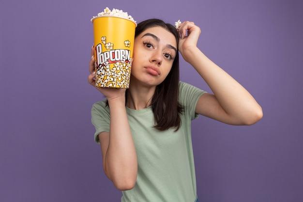 Mulher bonita jovem confiante segurando um balde de pipoca e um pedaço de pipoca tocando a cabeça com um balde de pipoca e a mão olhando para frente isolada na parede roxa com espaço de cópia