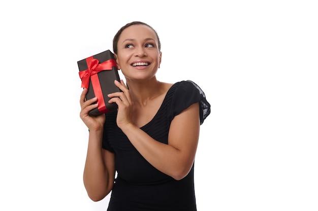 Mulher bonita, jovem, curiosa, mestiça, vestida de preto, segura uma caixa de presente perto da orelha e ouve o que ela contém, sorri com um lindo sorriso dentuço, isolada sobre um fundo branco com espaço de cópia