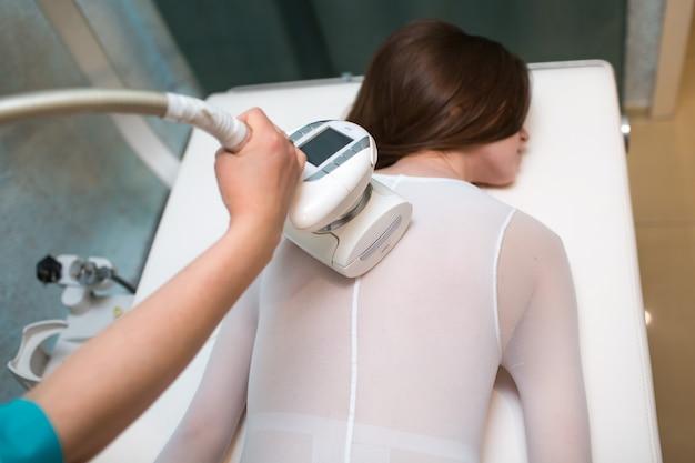 Mulher bonita jovem e glp massagem nas costas procedimento na clínica spa