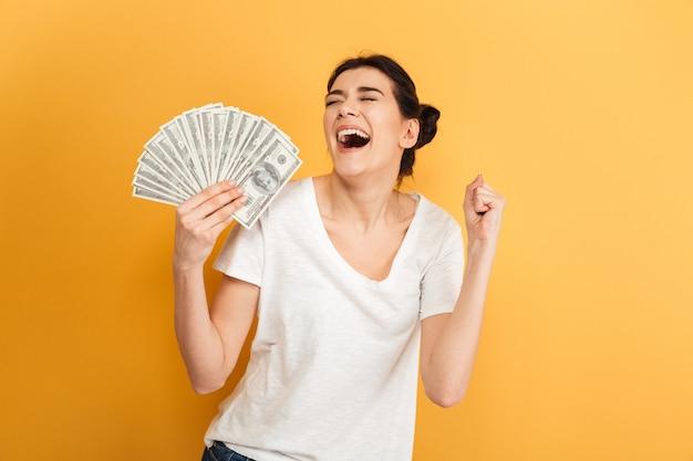Mulher bonita jovem emocional segurando dinheiro faz gesto de vencedor.
