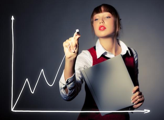 Mulher bonita jovem empresária desenha um gráfico