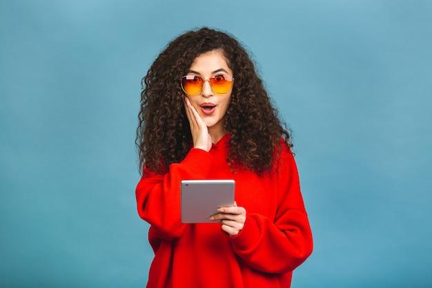 Mulher bonita jovem espantada animada com o tablet pc. garota feliz usando computador tablet, isolado sobre fundo azul.