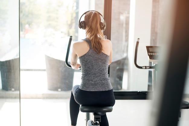 Mulher bonita jovem esporte é exercício de bicicleta no ginásio