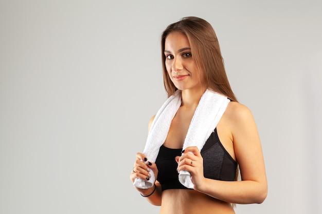 Mulher bonita jovem esportes posando com toalha no pescoço contra cinza