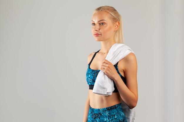 Mulher bonita jovem esportes posando com toalha no pescoço contra fundo cinza