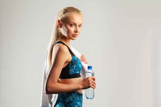 Mulher bonita jovem esportes posando com toalha no pescoço