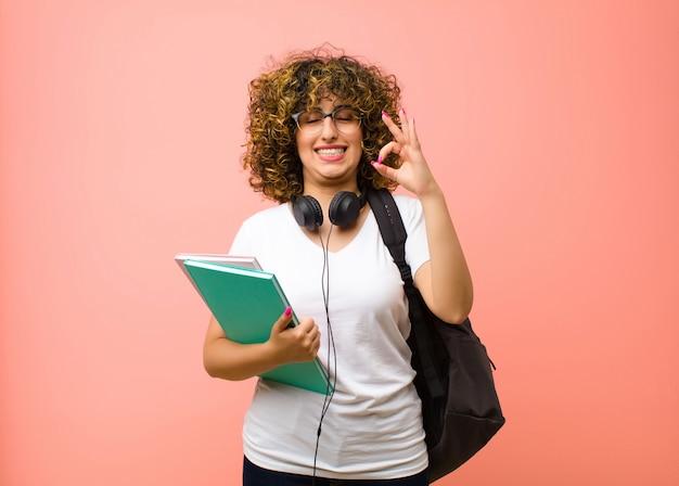 Mulher bonita jovem estudante olhando concentrado e meditando, sentindo-se satisfeito e relaxado, pensando ou fazendo uma escolha contra a parede rosa