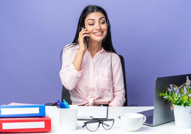 Mulher bonita jovem feliz em roupas casuais usando fone de ouvido, sorrindo confiante enquanto fala no celular, sentada à mesa com o laptop sobre fundo azul, trabalhando no escritório