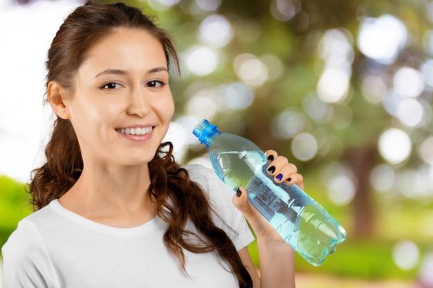 Mulher bonita jovem fitness com forma de corpo perfeito, bebendo água fresca