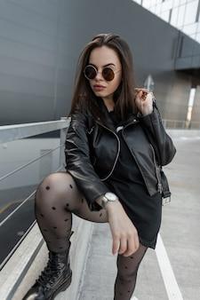 Mulher bonita jovem legal hippie em óculos redondos da moda com jaqueta de couro preta da moda e vestido com meia-calça sexy segura uma bolsa e posando na cidade