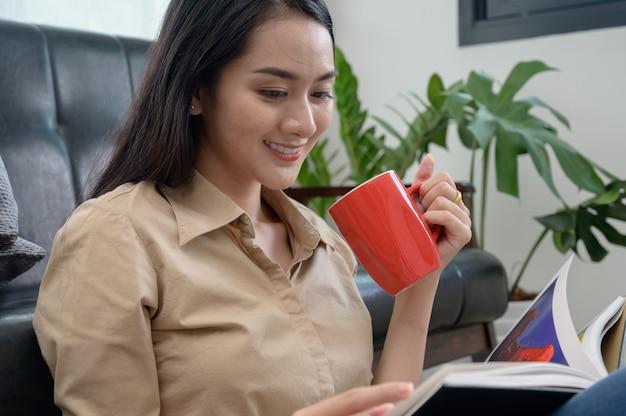 Mulher bonita jovem pele branca asiática sentado tomando café e lendo um livro goza de descanso