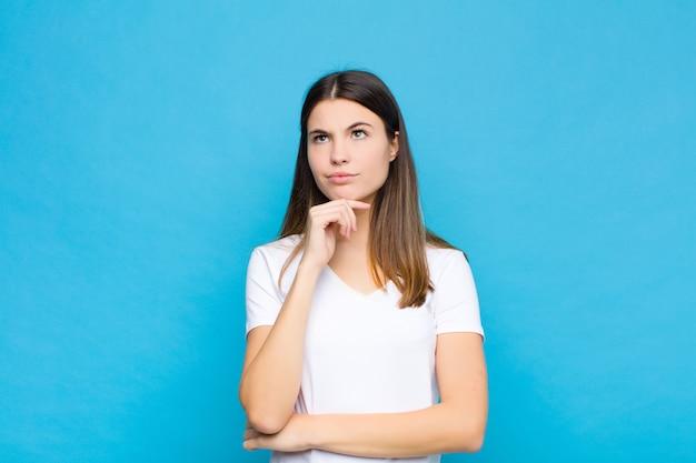 Mulher bonita jovem pensando, sentindo-se duvidoso e confuso, com opções diferentes, imaginando qual decisão tomar contra a parede azul
