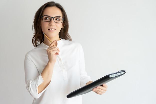 Mulher bonita jovem pensativa, segurando o arquivo e lápis