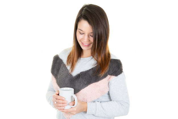 Mulher bonita jovem relaxante olhando para baixo segurando a xícara de café ou caneca de chá