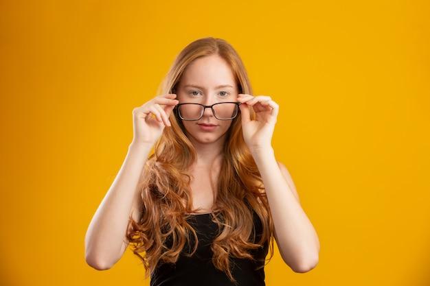 Mulher bonita jovem ruiva com cabelos cacheados feliz com os óculos dela. conceito de cuidado do olho. na parede amarela