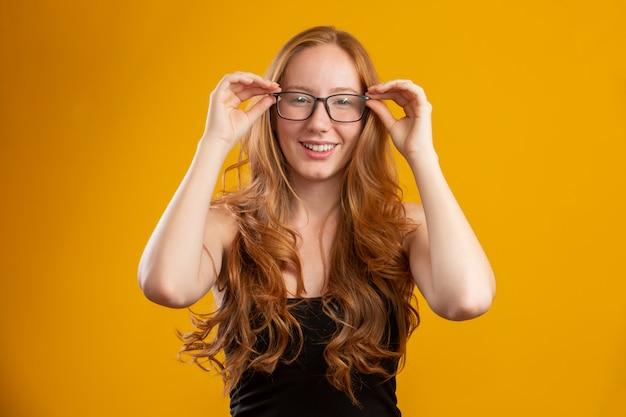 Mulher bonita jovem ruiva com cabelos cacheados feliz com os óculos dela. conceito de cuidado do olho.