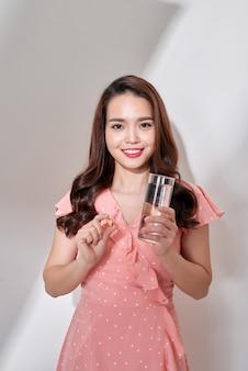 Mulher bonita jovem saudável tomando cápsulas pílula com água, maquiagem natural de rosto de beleza, isolada sobre fundo branco.