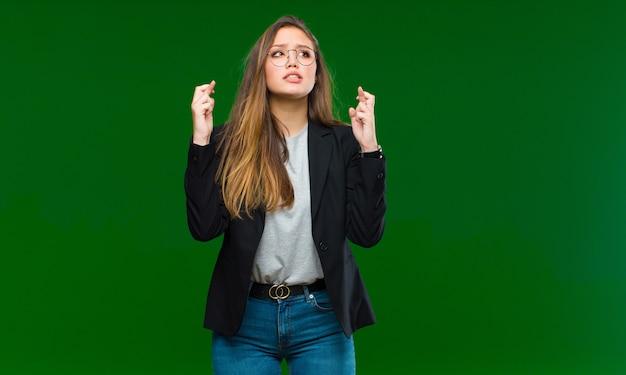 Mulher bonita jovem se sentindo confusa e sem noção, pensando em uma explicação ou pensamento duvidoso contra a parede verde