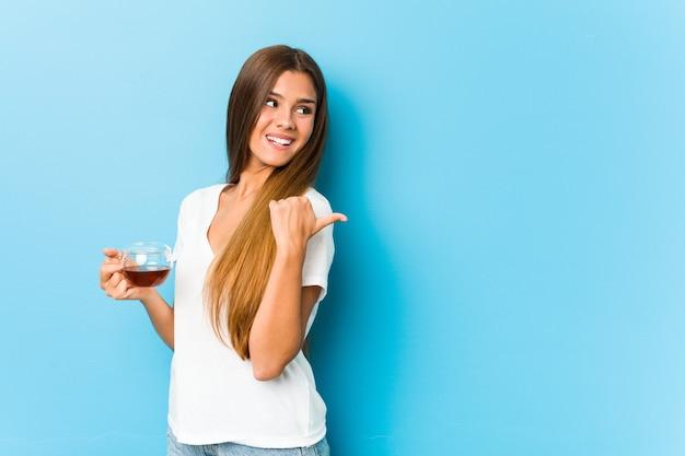 Mulher bonita jovem segurando uma xícara de chá aponta com o dedo polegar, rindo e despreocupada.