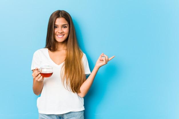 Mulher bonita jovem segurando uma xícara de chá, sorrindo e apontando de lado, mostrando algo no espaço em branco.