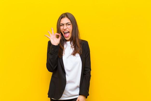 Mulher bonita jovem, sentindo-se bem-sucedida e satisfeita, sorrindo com a boca aberta, fazendo sinal bem com a mão contra a parede laranja