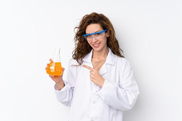 Mulher bonita jovem sobre parede isolada com um tubo de ensaio científico e apontando-o