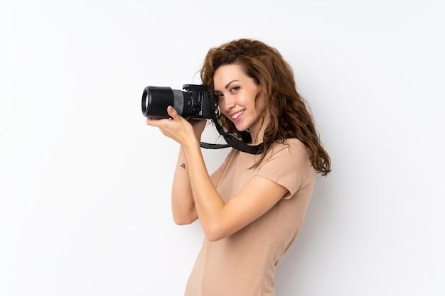 Mulher bonita jovem sobre parede isolada com uma câmera profissional