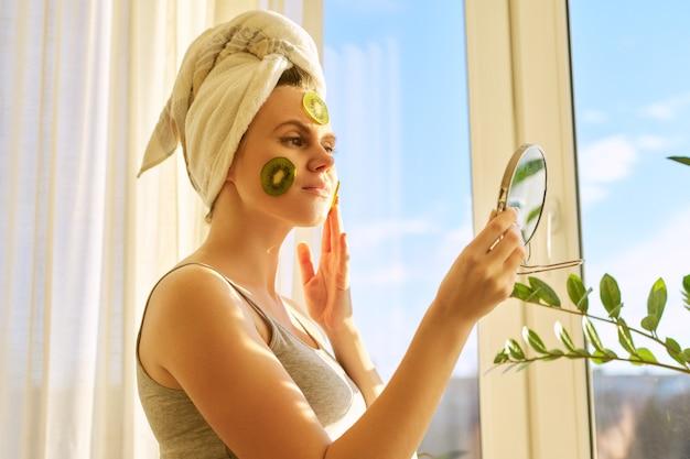 Mulher bonita jovem sorridente fechar em casa perto da janela com máscara facial de fruta caseira natural de kiwi no rosto, toalha na cabeça. cuidados com a pele, cosméticos, cosmetologia, dermatologia.