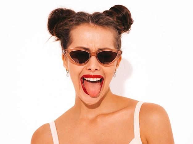 Mulher bonita jovem sorridente sexy hipster com lábios vermelhos em óculos de sol. na moda garota no maiô de moda praia de verão.