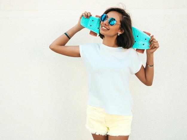 Mulher bonita jovem sorridente sexy hipster em óculos de sol. garota na moda em t-shirt e shorts de verão. mulher positiva com skate centavo azul posando na rua perto da parede branca