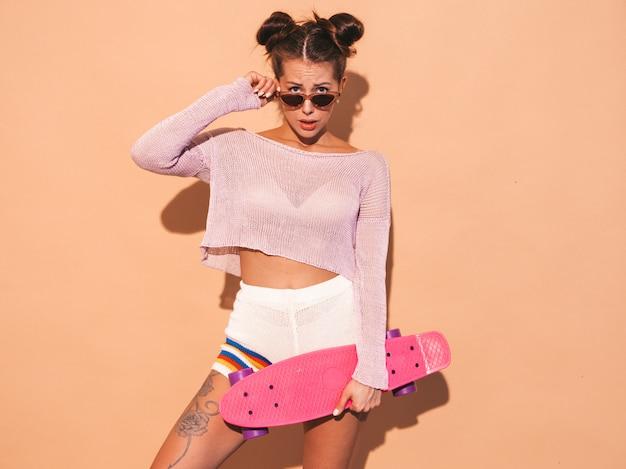 Mulher bonita jovem sorridente sexy hipster. menina na moda no tópico de casaco de malha de verão, shorts. fêmea positiva enlouquecendo com skate centavo rosa. tirando os óculos de sol. dois chifres