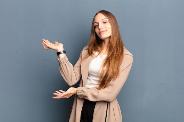 Mulher bonita jovem sorrindo com orgulho e confiança, sentindo-se feliz e satisfeito e mostrando um conceito no espaço da cópia sobre parede cinza