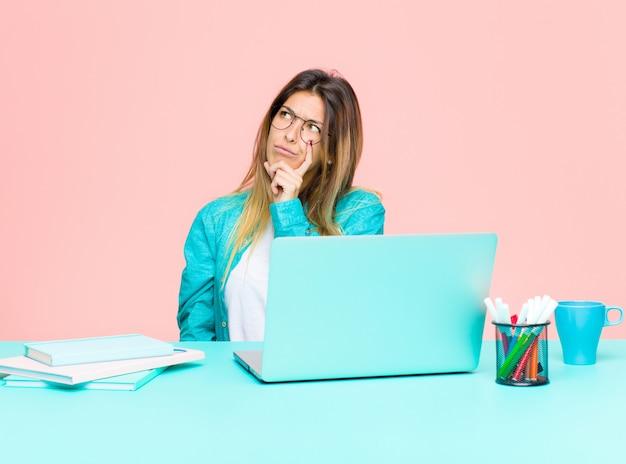 Mulher bonita jovem trabalhando com um laptop com um olhar concentrado, pensando com uma expressão duvidosa, olhando para cima e para o lado
