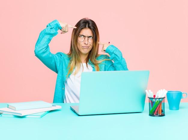 Mulher bonita jovem trabalhando com um laptop com um olhar sério e concentrado