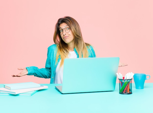 Mulher bonita jovem, trabalhando com um laptop, confusa e confusa, insegura sobre a resposta ou decisão correta tentando fazer uma escolha