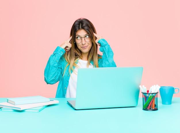 Mulher bonita jovem trabalhando com um laptop olhando concentrado e pensando seriamente em uma idéia imaginando uma solução para um desafio ou problema