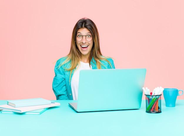 Mulher bonita jovem trabalhando com um laptop olhando feliz e agradavelmente surpreendido, animado com uma expressão fascinada e chocada