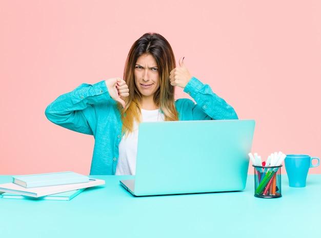Mulher bonita jovem trabalhando com um laptop se sentindo confusa, sem noção e insegura, ponderando o bom e o ruim em diferentes opções ou opções