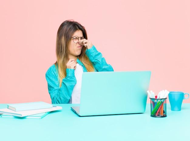 Mulher bonita jovem trabalhando com um laptop sentindo nojo, segurando o nariz para evitar cheirar um fedor sujo e desagradável