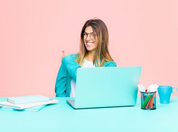 Mulher bonita jovem, trabalhando com um laptop, sentindo-se feliz, positiva e bem-sucedida
