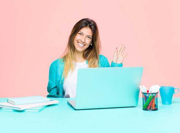 Mulher bonita jovem trabalhando com um laptop sorrindo feliz e alegremente, acenando com a mão, dando as boas-vindas e cumprimentando-o ou dizendo adeus